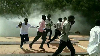 Students at the University of Khartoum attempt to escape from tear gas (File photo)