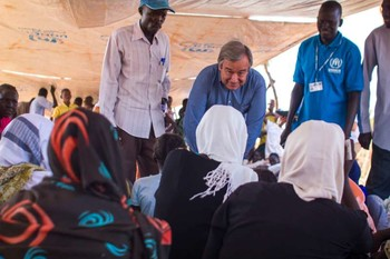 The then UN High Commissioner for Refugees (now UN Secretary-General) António Guterres speaks with a group of young women waiting to be registered at Yida refugee camp in South Sudan in 2012 (K. Mahoney/UNHCR)