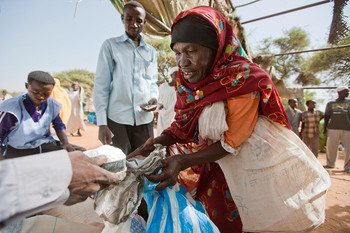 A woman receives sugar from the World Food Programme (WFP) in Kassab camp in 2012 (Unamid)
