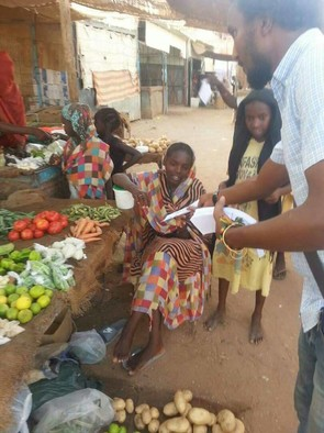 Anti-cholera campaigner hands out pamphlets to residents in Khartoum Bahri (RD)