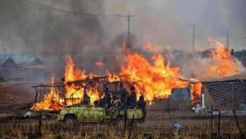 Militiamen drive by a village on fire in Sudan (file photo)