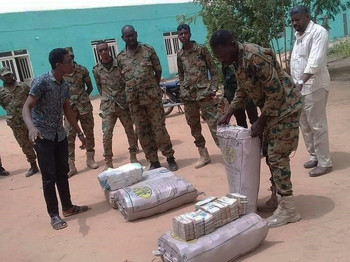 Officers display some of the cash hoard found at the residence of deposed President Omar Al Bashir yesterday