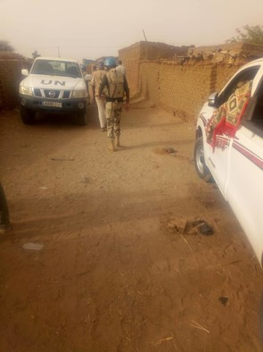 Unamid soldiers in Kalma camp yesterday. The car on the right contains the body of one of the victims, covered with a carpet (RD)