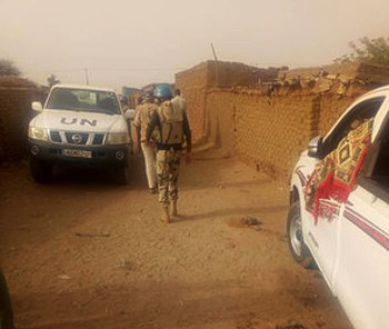 Unamid peacekeepers at the Kalma camp murder scene - the body of one of the victims is covered by a carpet in the car on the right (RD)