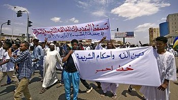 "Limited protests in Khartoum against law amendments. The banner in the front says ""God's religion and the Sharia form a red line"". (Social media)"