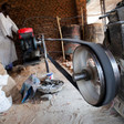 A man starts the engine of his automatic sorghum and millet mill in the El Mawashi market in El Fasher, North Darfur (Albert González Farran / Unamid)