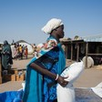 A South Sudanese mother carries a bag of cereals provide by the WFP in in El Agaya refugee camp in White Nile state (Ala Khier/WFP)
