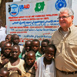 Steven Koutsis (R), the United States' top envoy in Sudan, posing for a picture with Sudanese children and villagers in Golo in Jebel Marra, Central Darfur (AFP)