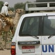 UNHCR convoy passes Sudanese man riding on a camel in Um Shalaya refugee camp near El Geneina, Darfur. (UNHCR file photo)