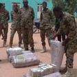 Officers display some of the cash hoard found at the residence of deposed President Omar Al Bashir on April 18, 2019 (SUNA)